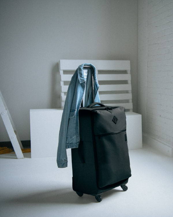 A Highland Luggage Carry-On Large in Black with a jacket slung over the extendable handle.